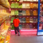 Photo: Small child looking at a wall of candy in a candy store