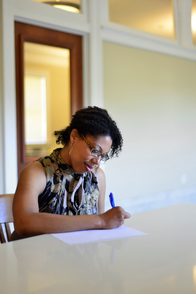 Mariam Williams, sitting at a table, pen in hand