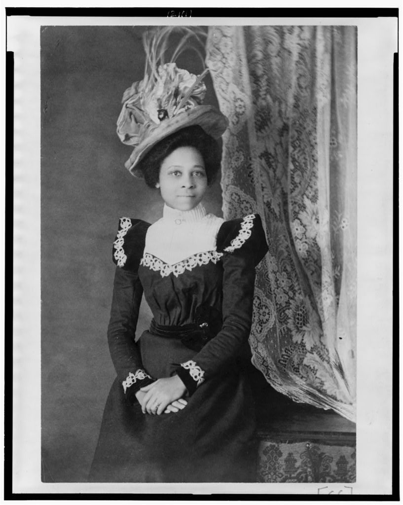 """Young African American woman, three-quarter length portrait, facing slightly right, with hands folded on her lap,"" Thomas E. Askew, 1899 or 1900"